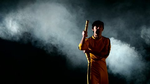 Costume Bruce Lee. the young man expertly twirling nunchaku.on black background. smoke, yellow clothing. Bruce Lee style.