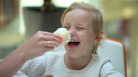 little girl funny cute girl smiling eating ice cream horn in shopping center. Happy family eats ice cream in mall. Closeup of face of cute blonde kid child holding ice-cream in hands. Child, children