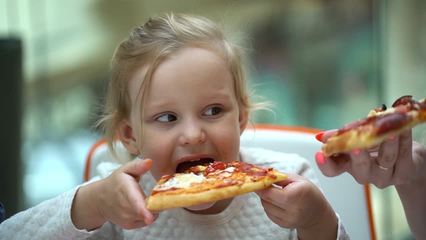 A small child in a fast food cafe eats pizza slice. Cute little kid girl portrait funny eating in fast food in mall. Cute little girl eating pizza. Hungry child taking bite from pizza delivery