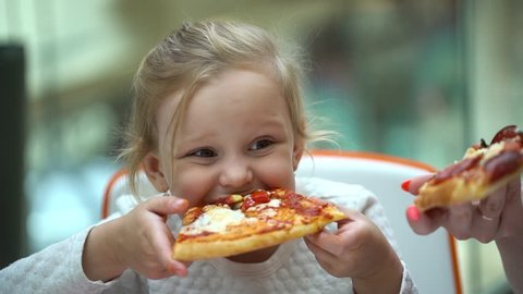 A small child in a fast food cafe eats pizza. Cute little kid girls portrait funny eating in fast food cafe in a mall. Cute little Caucasian girl eating pizza. Hungry child taking a bite from pizza