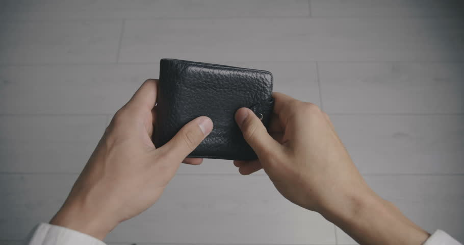 Close-up of a man's hand holding Leather Wallet Empty with No Money. The concept of poverty | Shutterstock HD Video #1016296948