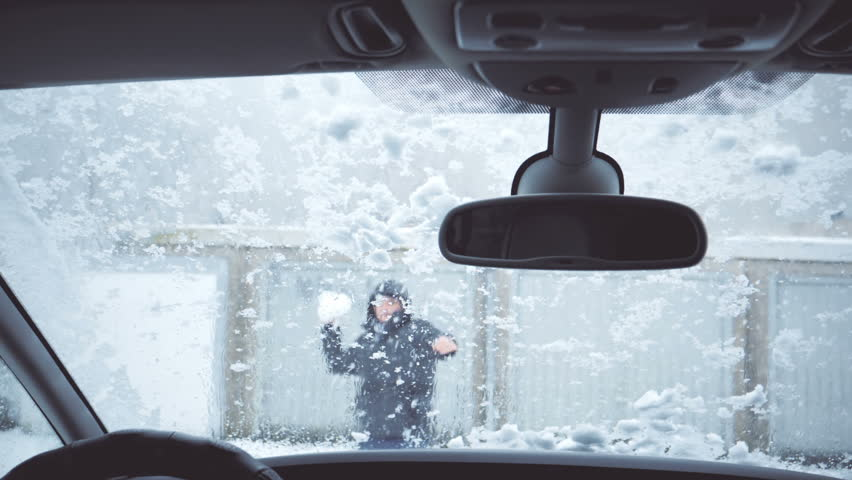 Man throwing snowball on windshield. Windscreen wiper cleaning snow.