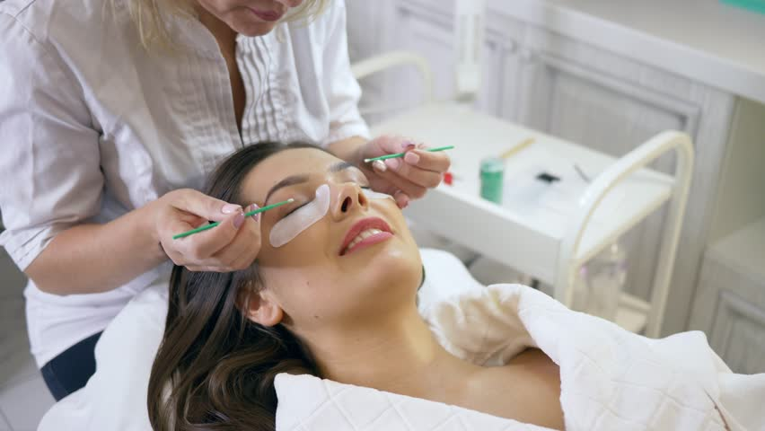 Eyelash extension, master prepares the client for the procedure in a beauty salon | Shutterstock HD Video #1016314588