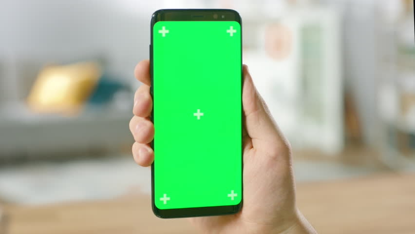 Close-up of a Man Holding Green Mock-up Screen Smartphone in His Hand. Using Modern Mobile Phone. In the Background Cozy Living Room or Home Office. Shot on RED EPIC-W 8K Helium Cinema Camera. | Shutterstock HD Video #1016316058