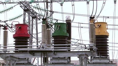 Electrical poles with wires and insulators at the electrical substation. Circuit breaker high voltage.  Part of high-voltage substation with switches and disconnectors.