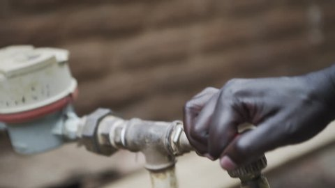 African Women Turning Water Tap On