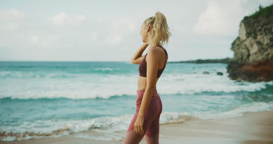 Fitness lifestyle of beautiful young woman at the beach | Shutterstock HD Video #1016378728