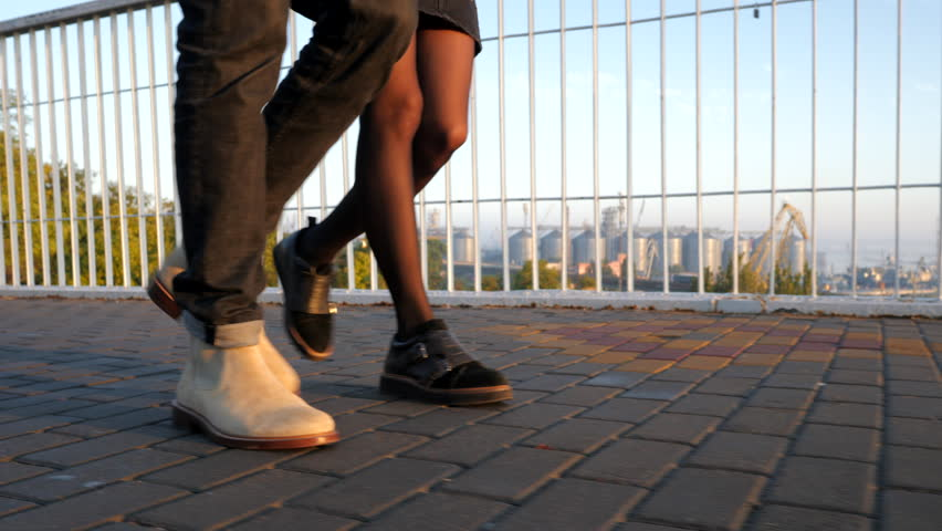 Legs of unrecognizable young couple walking on bridge at summertime. Sunset light. Stylish happy pair in business clothes holding hands on date through empty street. 4k | Shutterstock HD Video #1016384188