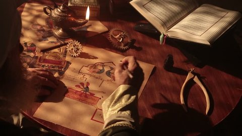 Old islamic scientist working in madrasah room. Old tools, reed pen, ink pot, papirus drawings and book of quran some scenes in dark and foggy enviroment.