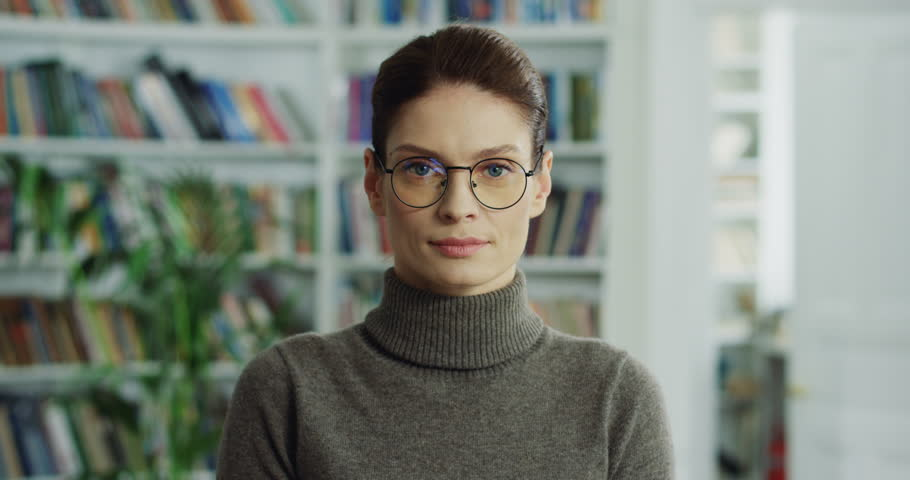 Close up of the beautiful Caucasian woman in glasses looking straight to the camera and smiling cheerfully. Portrait. | Shutterstock HD Video #1016395648