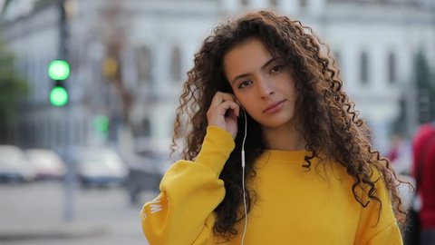 Portrait of young multiracial girl in yellow pullover puts on earphones in urban city background