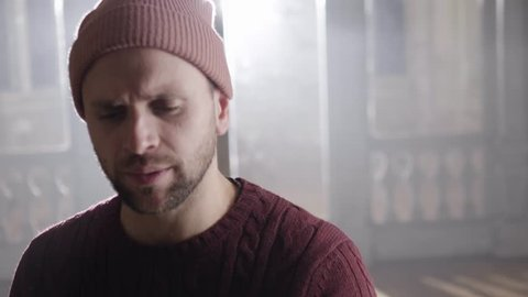 Dynamic camera showing young brown eyed man dressed in knitted pullover and ski hat actively rapping , looking at camera and moving back and forward during action in empty bright room.