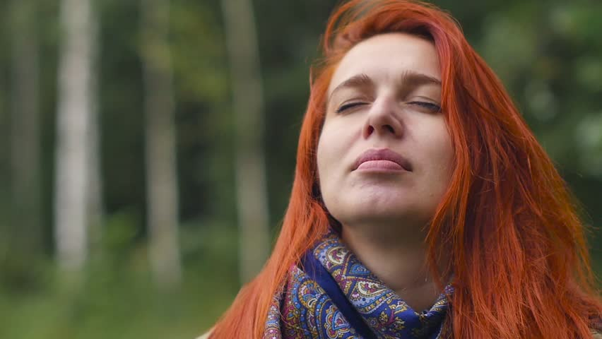 A young woman breathes clean air, looks at the sky with a smile, closes her eyes with pleasure | Shutterstock HD Video #1016410318