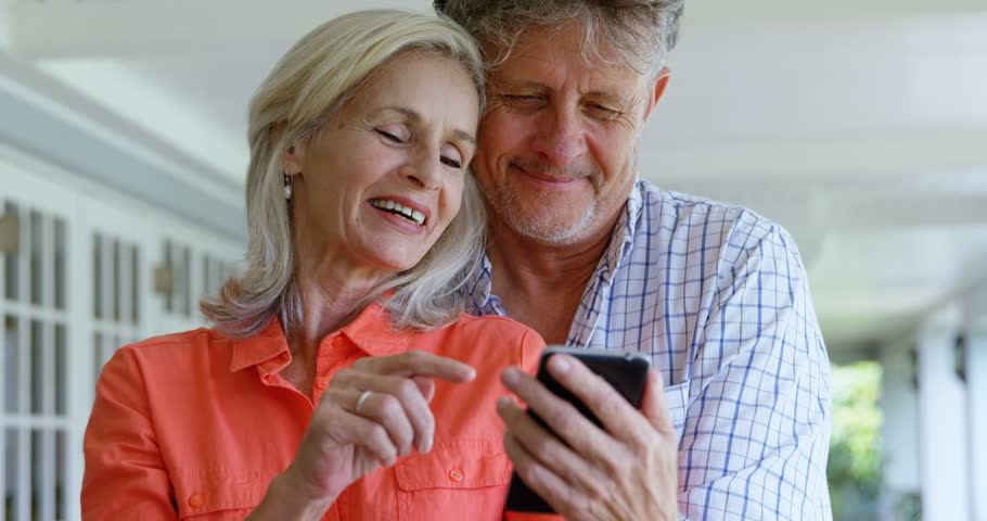 Front view of senior Caucasian couple using mobile phone on the porch at home