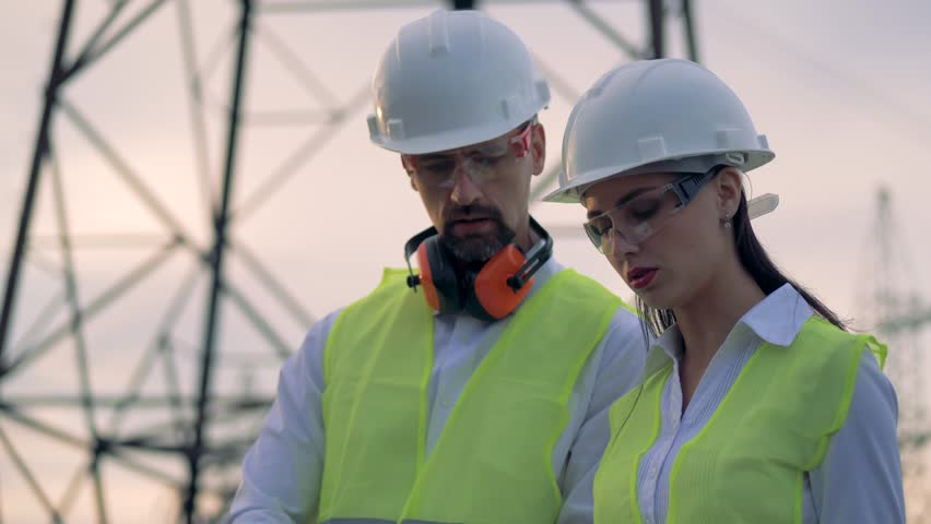 Engineers working near transmission lines. 4K. | Shutterstock HD Video #1016449138