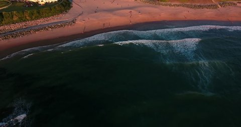 AERIAL VIEW of the Basque coast during golden hours with surfers and vacationers in Biarritz