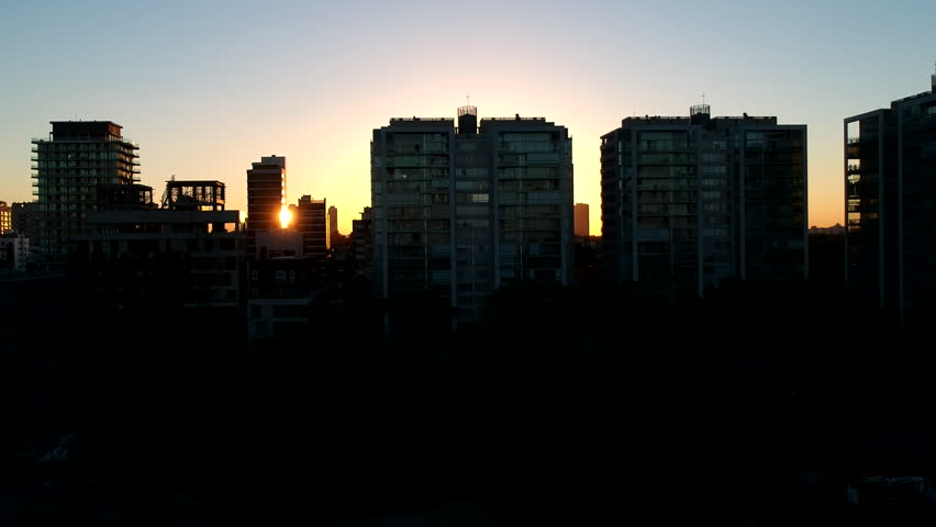 Drone flying upwards in front of sunlight through buildings   Shutterstock HD Video #1016483218