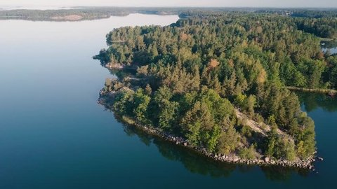 Sunny summer morning in Sweden. Aerial view from the Swedish archipelago. Drone flies forward over a small island with a green forest. Beautiful blue colour of the ocean.