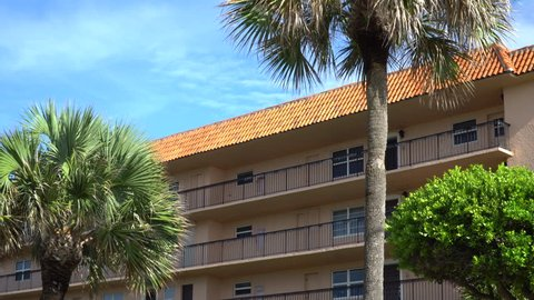Day time exterior establishing shot of generic hotel condo or apartment building in tropical location with palm trees outside under clear blue sky. 4K DX stock video