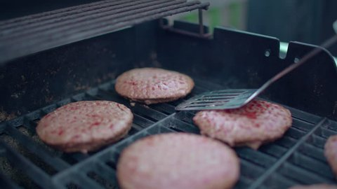 Close up of spatula flipping hamburgers on barbecue