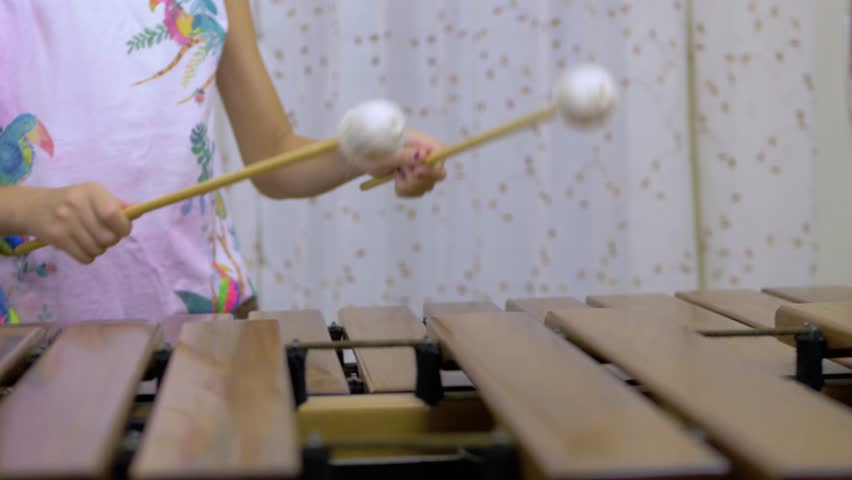 A girl is playing marimba with two mallets. Practicing music at home. Keyboard percussion instrument with wooden keys.