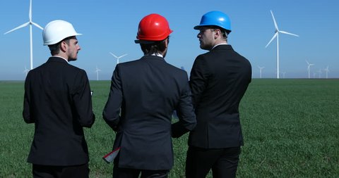 Team of Workers Talking Looking Over Plans Together Visiting Wind Turbines Field