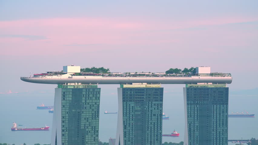 SINGAPORE - OCT 19, 2017: Amazing view of Marina Bay Sands hotel with swimming pool and restaurant on roof. Sunset zooming out panorama of beautiful resort in central district of modern Asian city