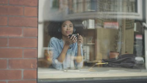 African American woman listening to headphones in Cafe coffee shop