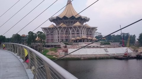 September 21, 2018 - Kuching Waterfront, Malaysia. Local people and foreign tourists come here to enjoy view of crossing bridge and boat or ferry cruise at waterfront in Malaysia.