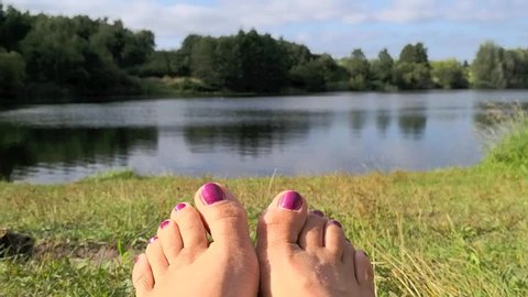 Woman at the lake in summer, moving her toes