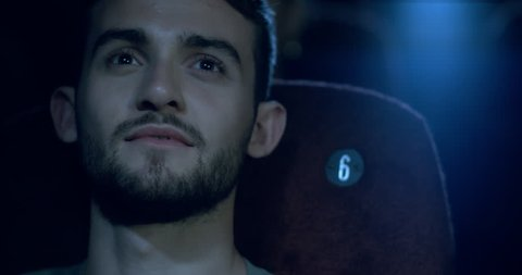 Close up of relaxed young man watching a film at the movie theatre