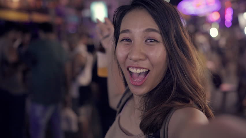 Backpacker Asian women blogger traveling drinking alcohol or beer and dancing with friends and using smartphone or camera photo and recording making vlog video in street night in Bangkok, Thailand.