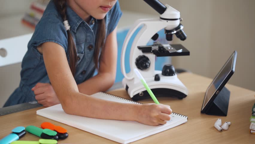 Schoolgirl doing homework, looking through a microscope. | Shutterstock HD Video #1016785168