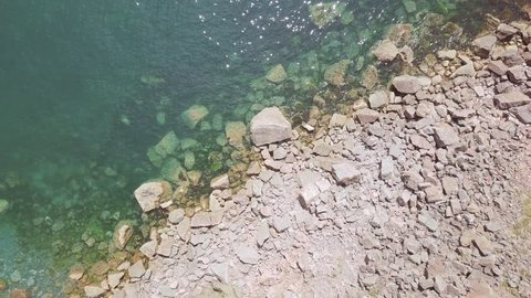 Overhead view of beautiful clear ocean water and rocks at Torquay, England.