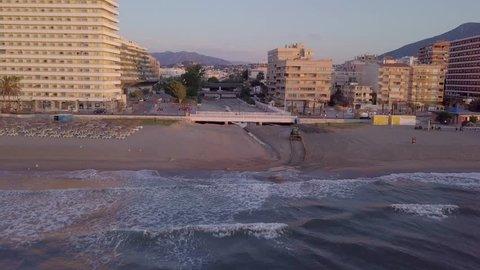 Spanish coastal city during sunrise - fly left and up