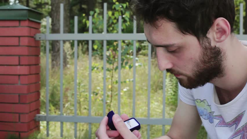 Young bearded guy in white t-shirt opens small blue velvet box with diamond wedding ring and takes it out on background of wooden fence with brick column in daylight.