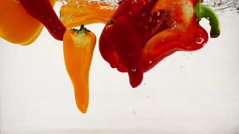 Red and orange peppers fall into the water with splashes and bubbles, slow motion close-up