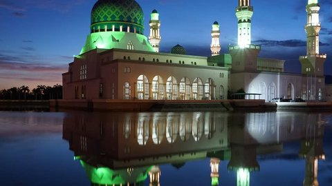 Timelapse of sunrise scenery near Likas Mosque or known as Masjid Bandaraya Likas in Sabah, Malaysia. Reflection on water. Camera zooming out