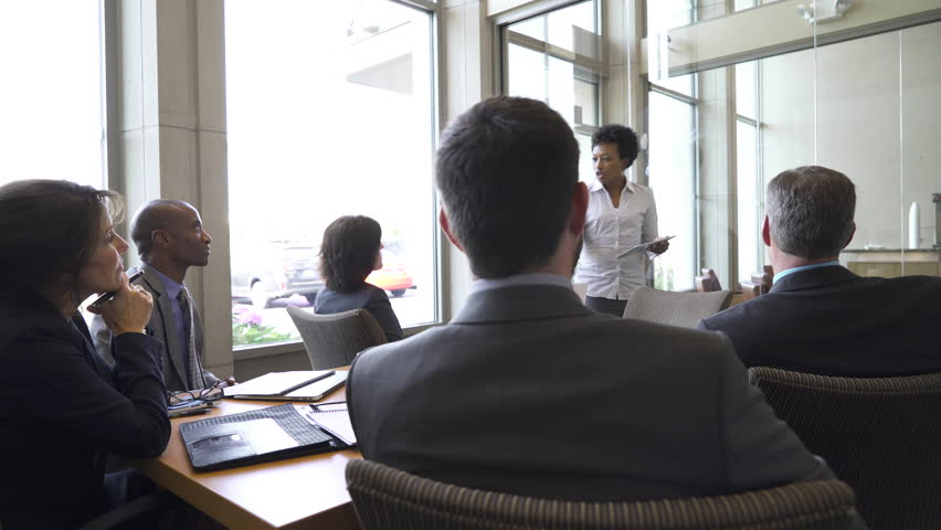 Businesswoman writing on glass while giving presentation in board room | Shutterstock HD Video #1016875348