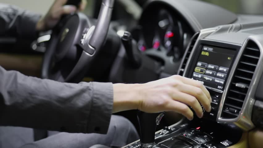 Man pushes mechanical and sensor buttons on screen in modern car #1016943718