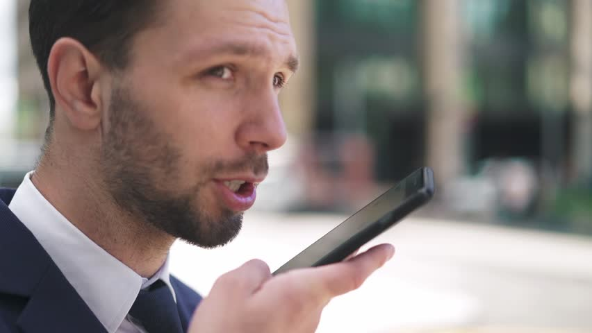 Hansome young caucasian businesman with fair hair and beard wearing a dark suit and tie talking on smartphone and smiling on a summer day. Hanheld slow motion medium shot | Shutterstock HD Video #1016949058