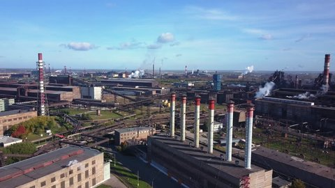 Drone panning of industrial park, many smoke stack pipes of steel plant, technogenic landscape with autumn bright trees, concept of pollution, air emissions from manufacturing sector, industrial city