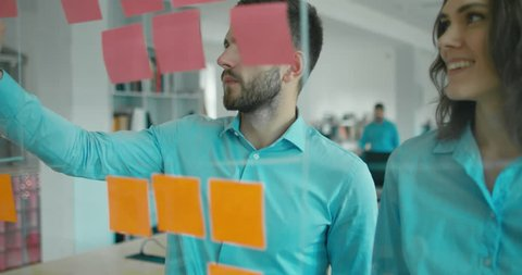 Caucasian colleagues standing near glass wall with sticky notes, framework for managing work, scrum methodology. 4K UHD 60 FPS SLOW MOTION