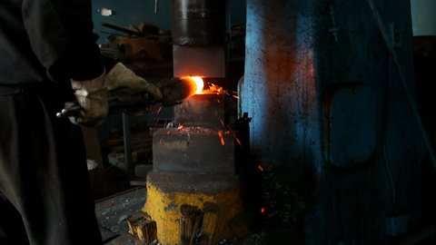 Blacksmith in the forge forges a metal part for mechanical engineering, hot metal and scale, slow motion, forge