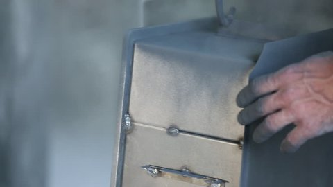 Painting of the safe. The employee the special equipment paints the safe. The safe is suspended over a floor on hooks. Close up. The employee's hands are visible. There is no person in a shot.