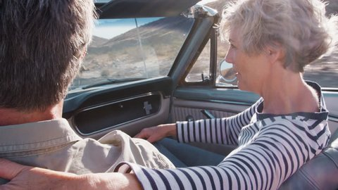 Senior couple in open car, woman in passenger seat, close up