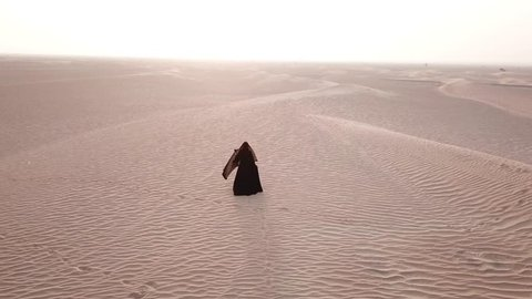 A woman in abaya (United Arab Emirates traditional dress) walking on the dunes in the desert in bright morning light towards the sun. Dubai, UAE.