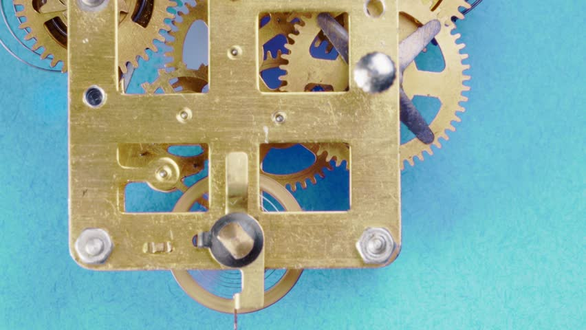 Close up detail of running clock or watch machinnery on a bluebackground. Copy space available and suitable for time concepts as time goes by, Daylight saving time or growing old.