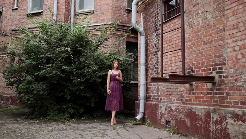 Very beautiful girl posing in the old courtyard of brick houses. #1017065218