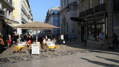 Lisbon, Portugal - September 28, 2018: Customers and pedestrians relaxing at a pavement cafe near Praca da Figueira, Chiado, Lisbon, Portugal